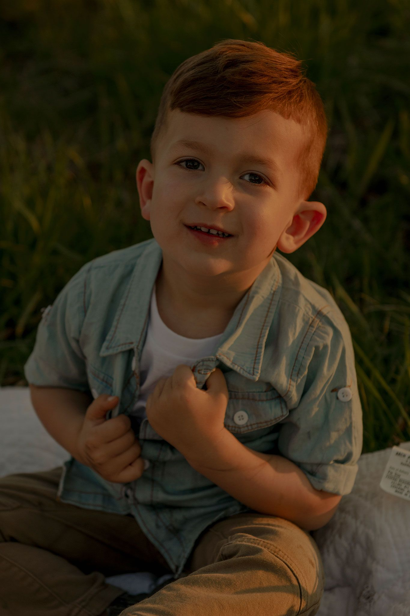 little boy staring at camera, while sitting on blanket during sunset at family session