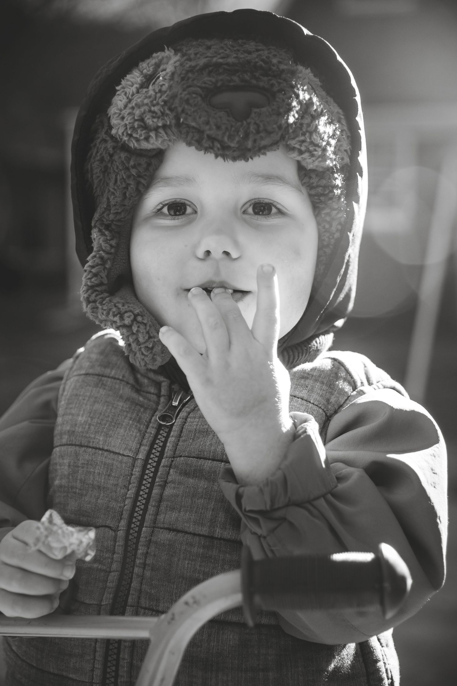 boy eating candy while looking at camera wearing hat and winter jacket while riding bike with flash illuminating behind