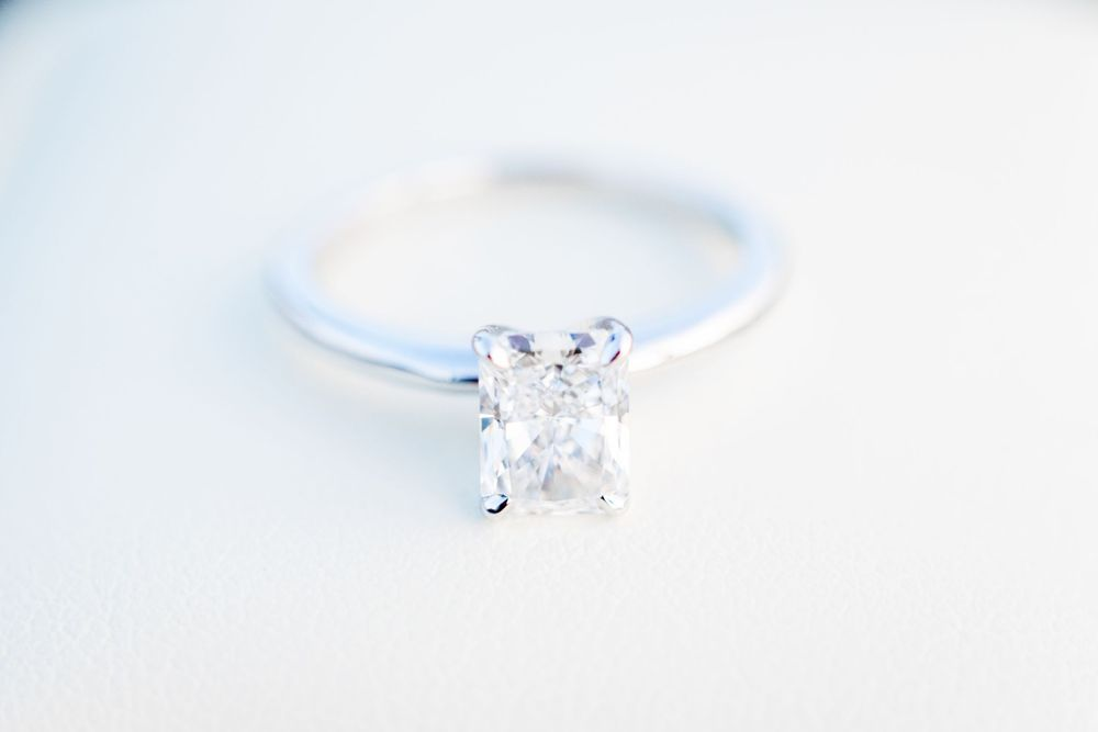 rectangle diamond and white gold engagement ring on top of white ring box by Chicago proposal photographer