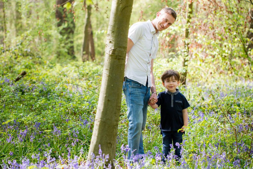A young boy holds his dad's hand in a bluebell wood - Family photography