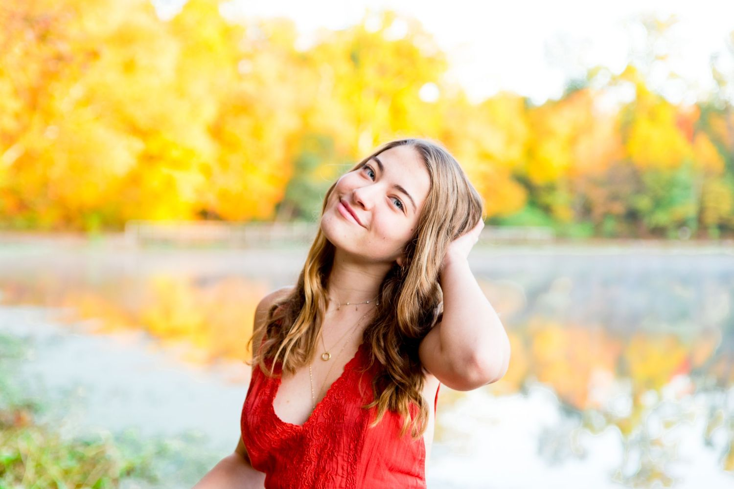 young woman in orange shirt plays with hair and smiles in front of a pond in Chicago with yellow trees behind her