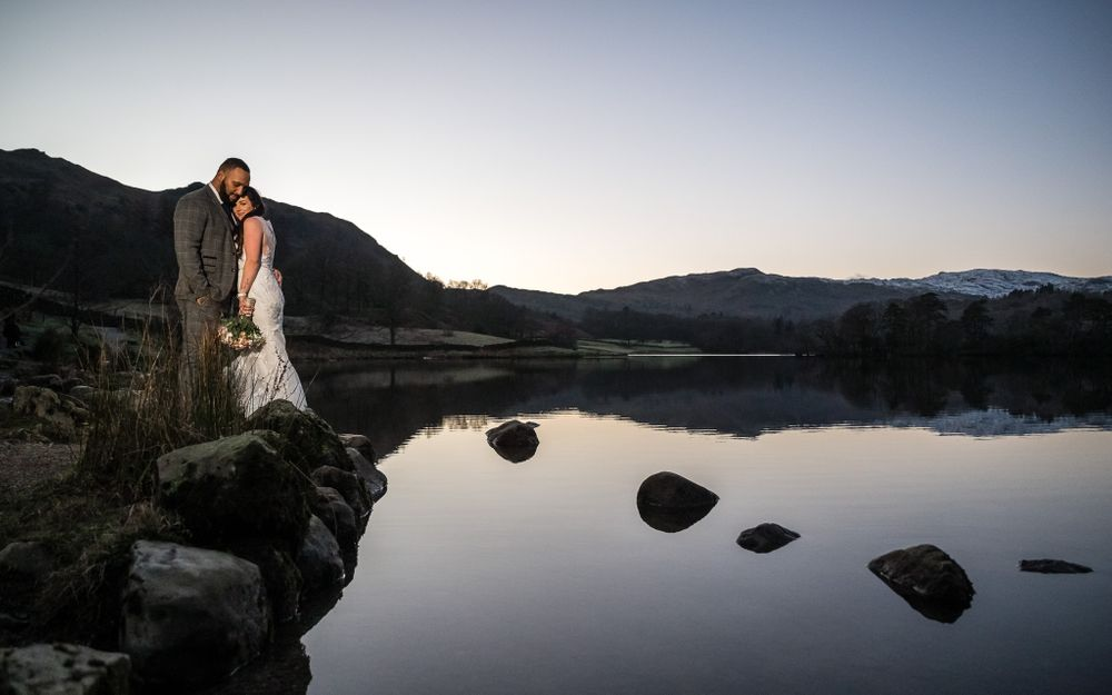 Bride and groom beside Rydal Water as sun goes down