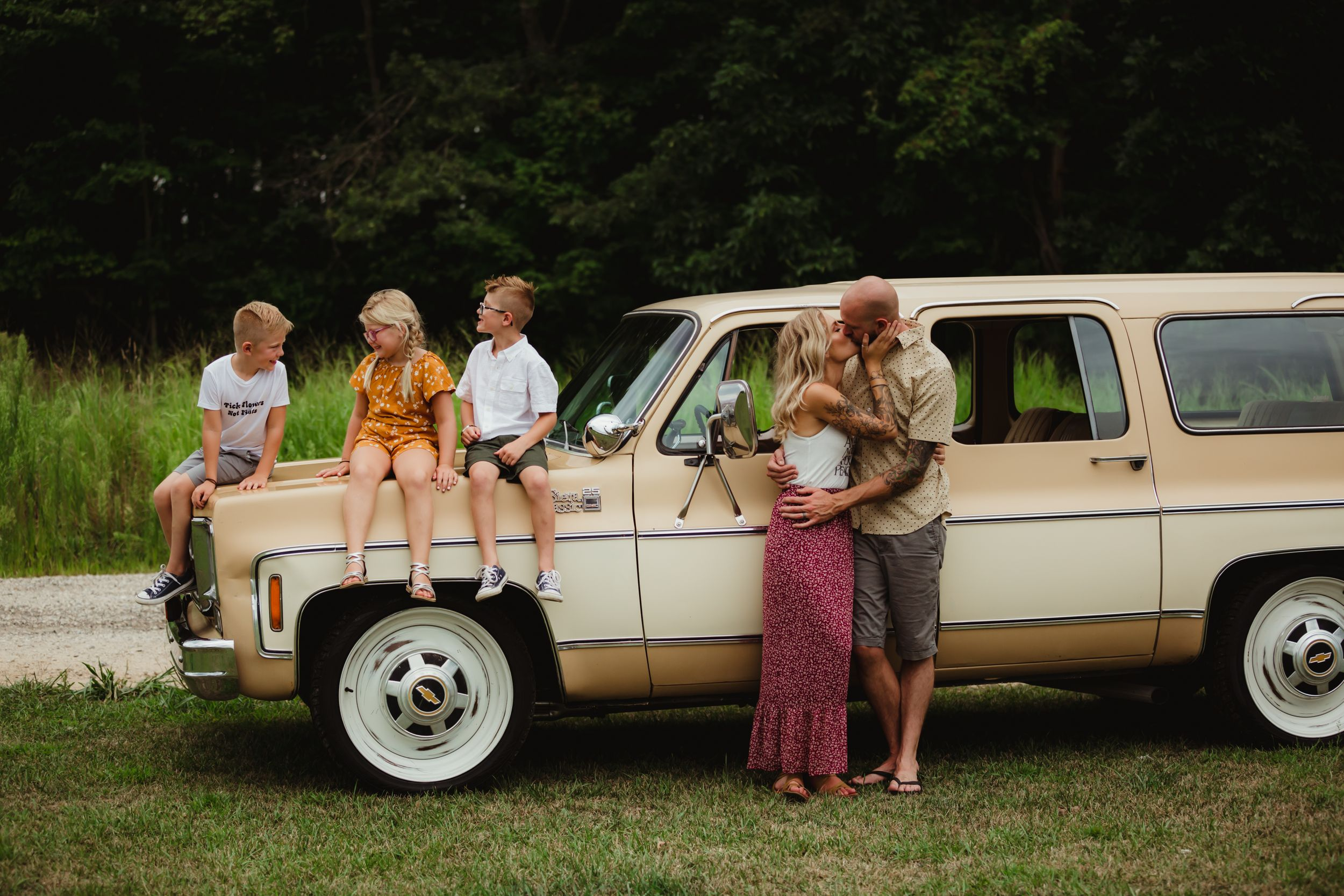 Three kids sitting on the hood of a station wagon while parents stand beside it and kiss.