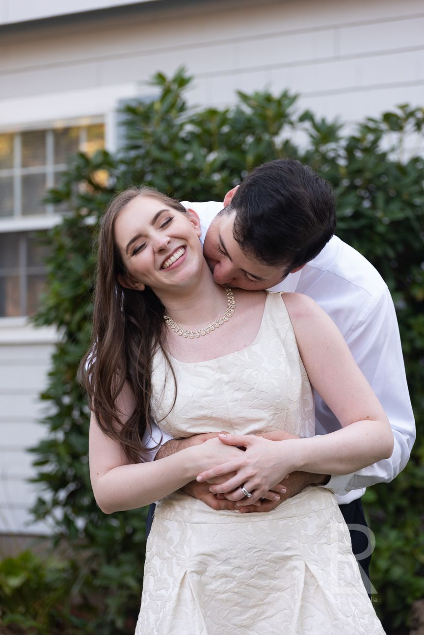 Leah Ramuglia Photography a groom kisses his bride on the neck at home after their Massachusetts wedding