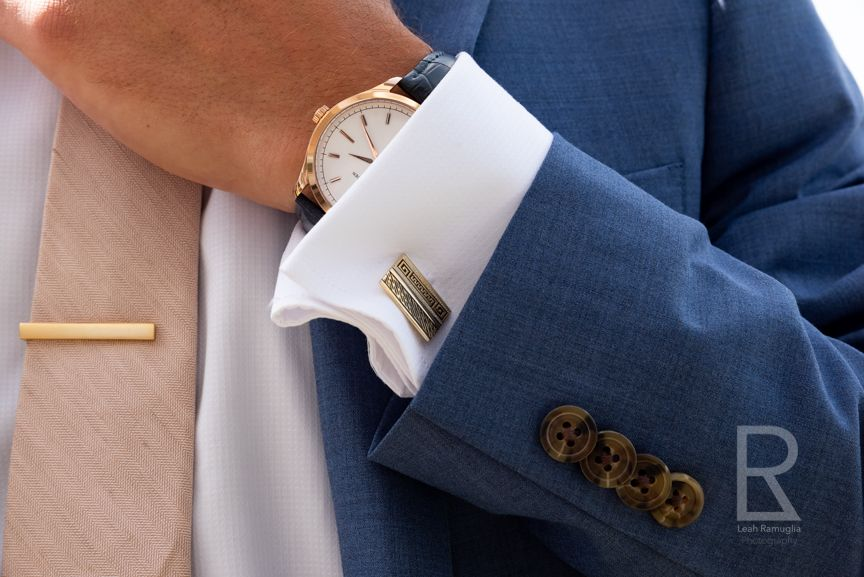 Leah Ramuglia Photography a groom adjust his tie on his blue suite with gold tie clip, watch, and cuff links