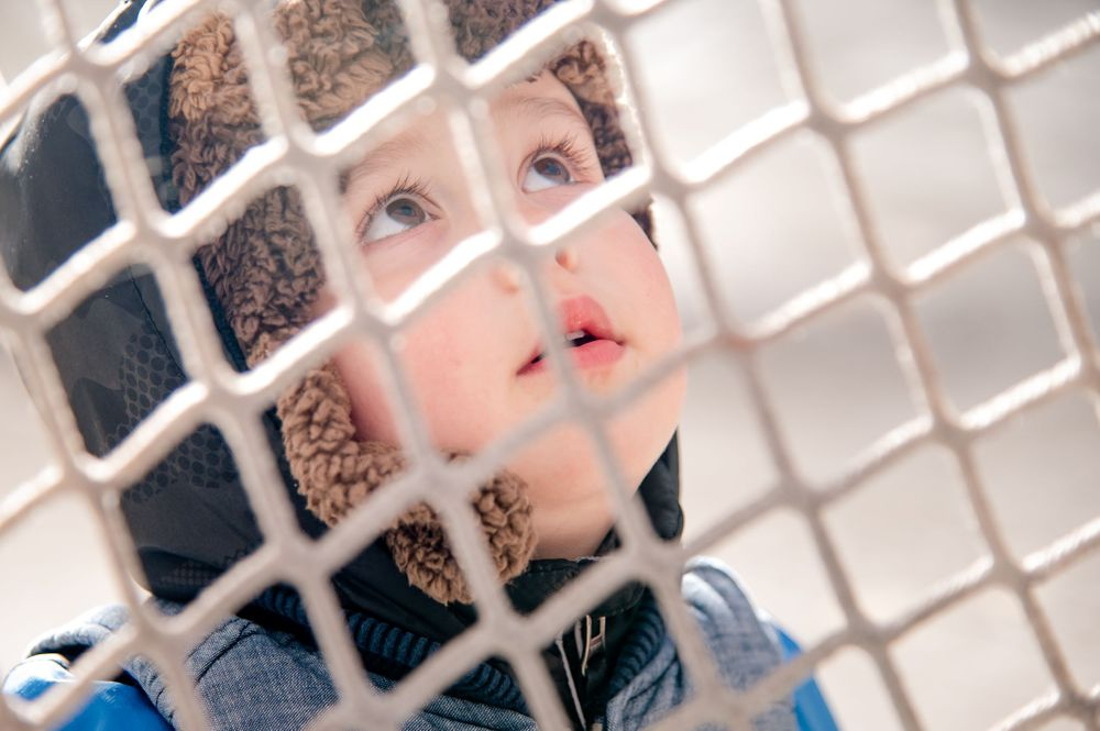 toddler with bear hat looking up into hockey net