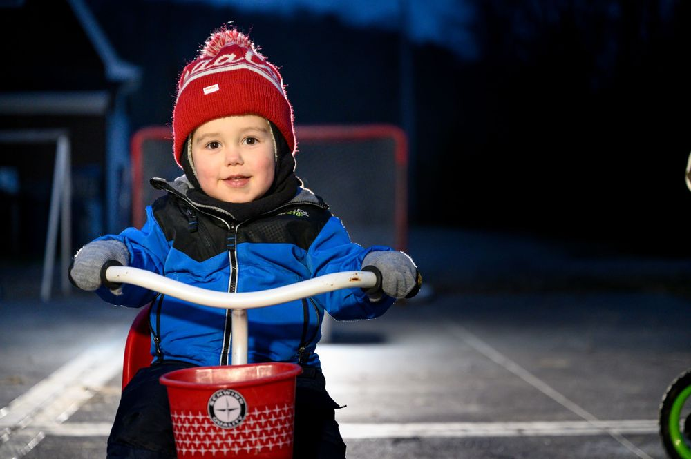 toddler on tricycle in winter at night riding bike around hockey net in pittsburgh