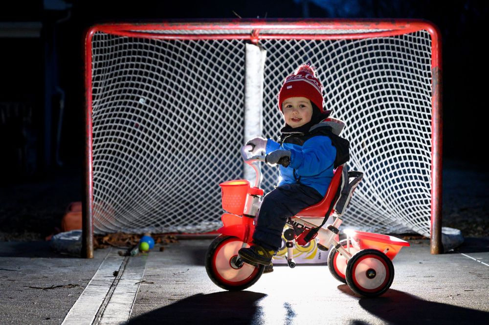 toddler on red tricycle in front of hockey net at night in winter