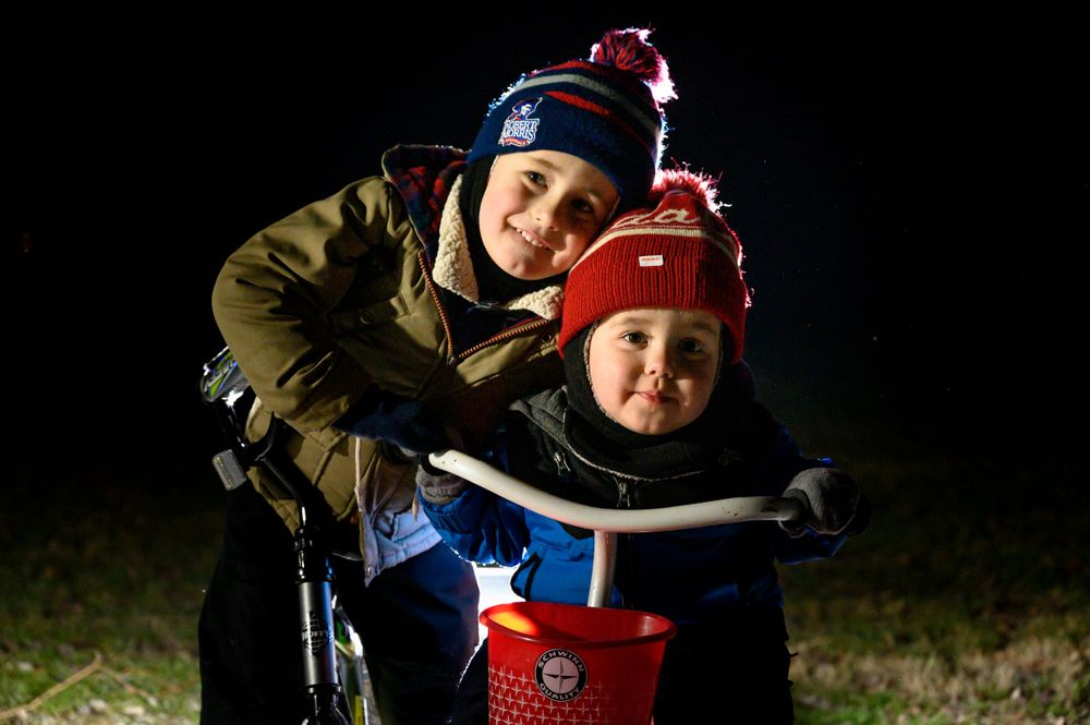 toddler boys on bike and tricycle in winter at night on cold winter night