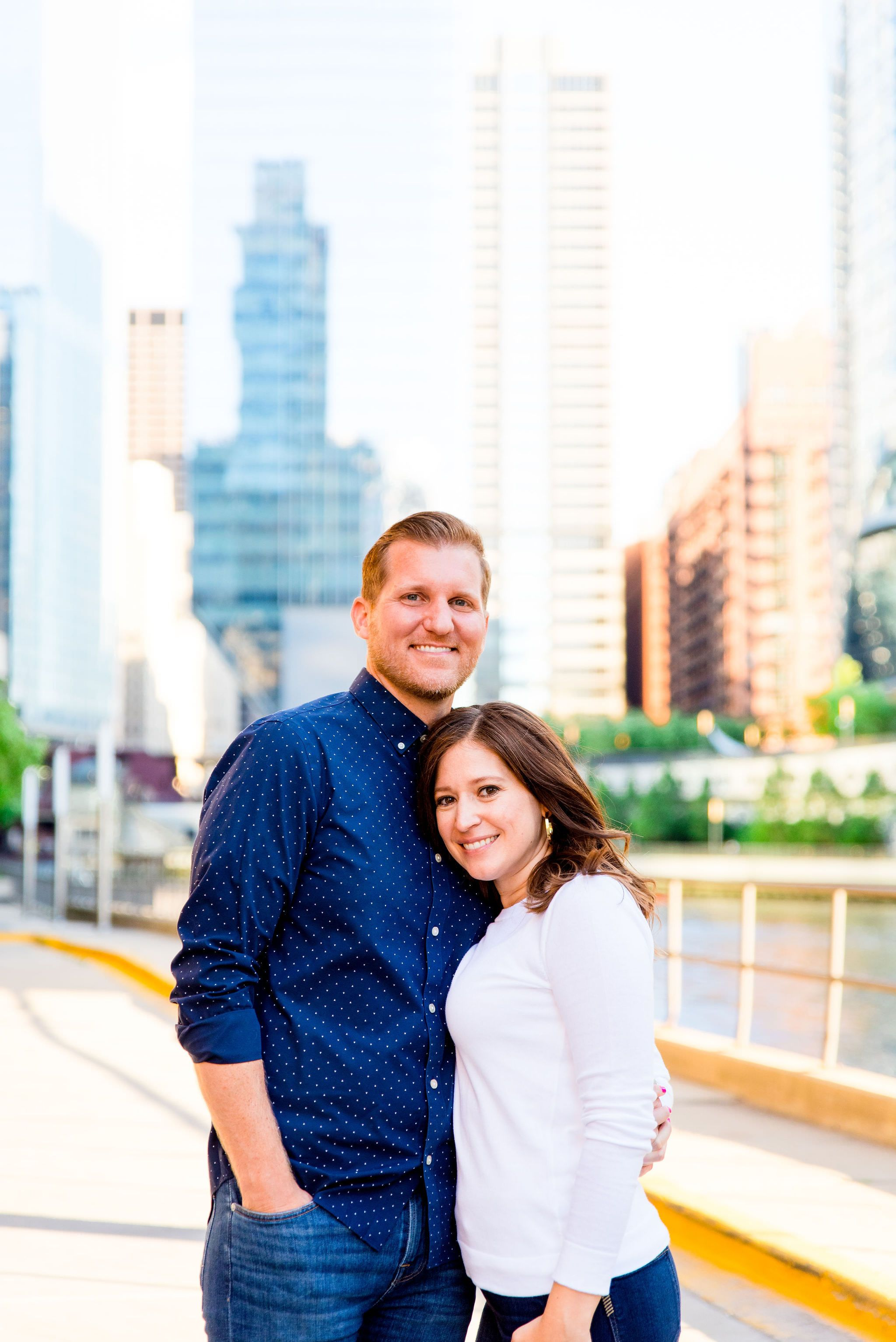 man and woman standing together smiling near River North Kinzie St Bridge engagement pictures