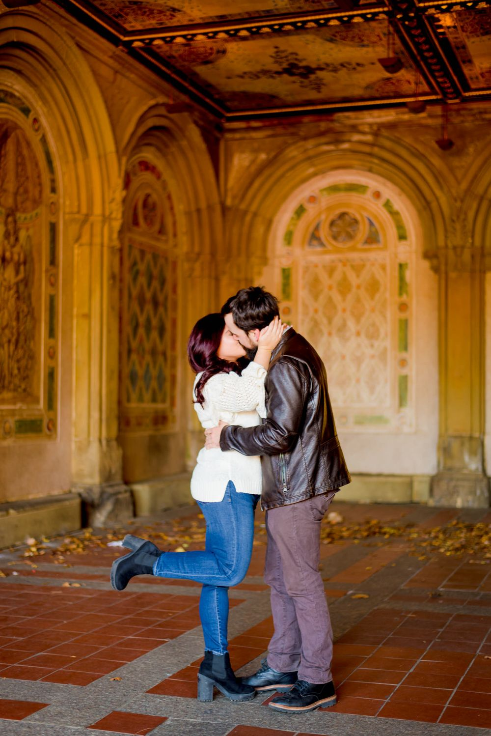 man in brown jacket and woman in white sweater kissing and hugging at Bethesda Terrace in Central Park for engagement