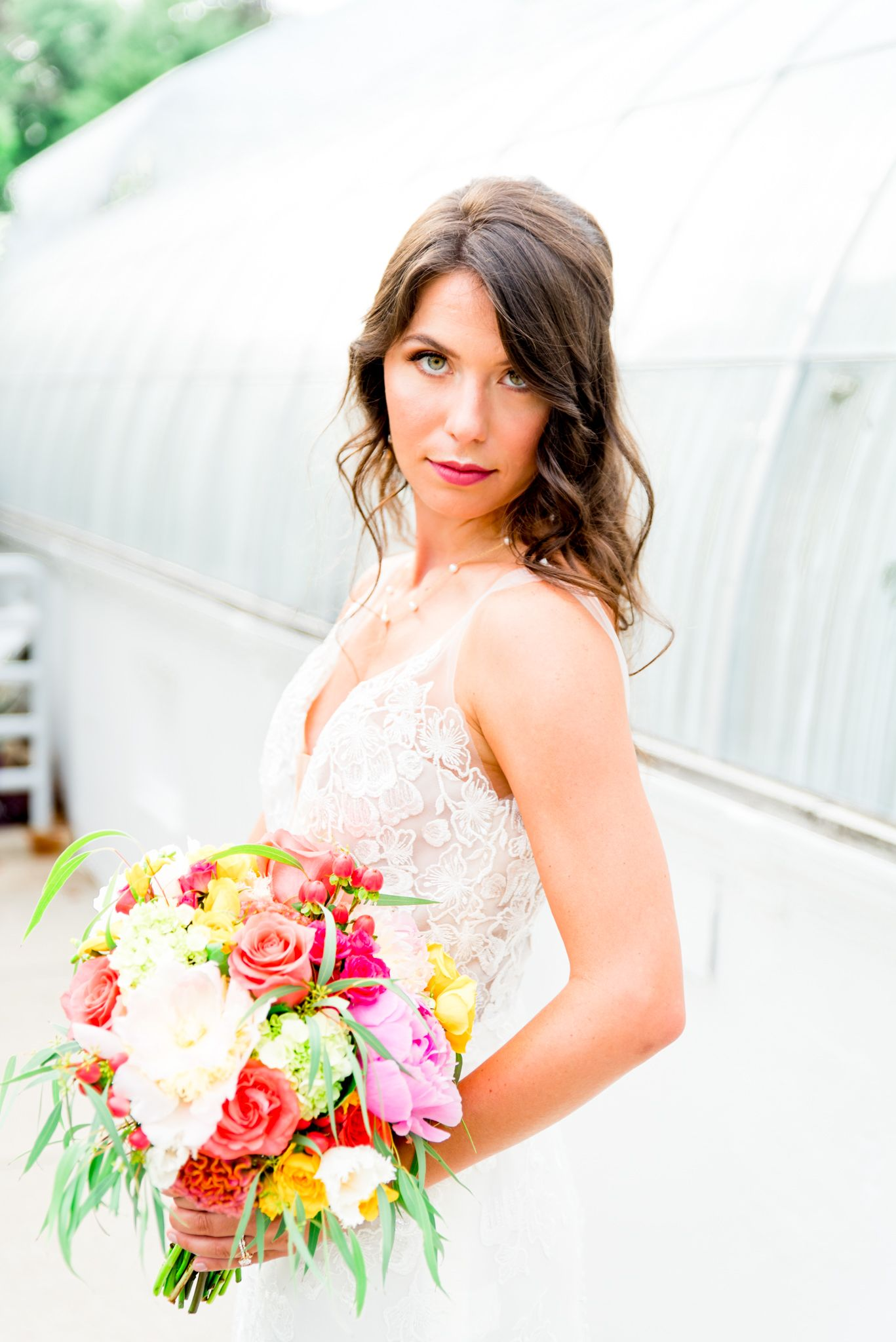 bride with brown hair green eyes and hot pink lipstick wears the Kelly Faetanini Serafina gown in front of Krohn