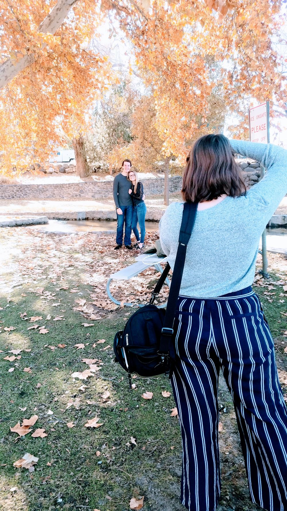 The back of a woman taking the photo of a couple in the fall foliage