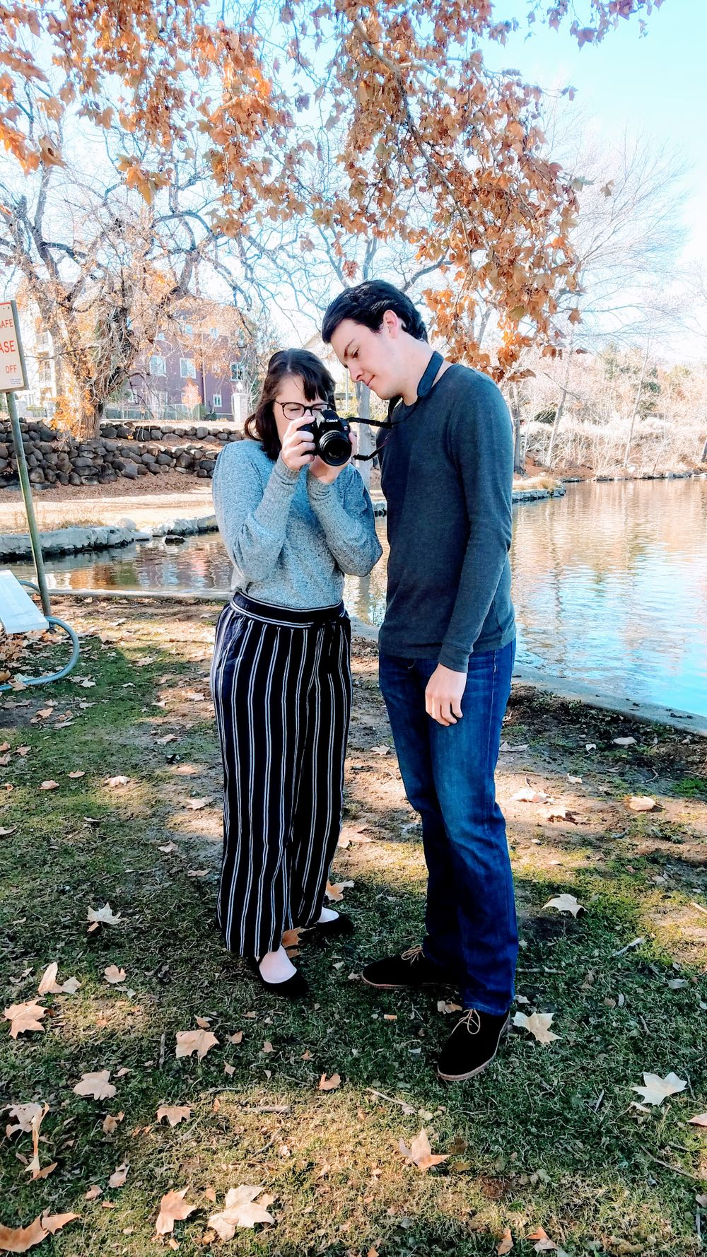 Brother and sister looking at photos on a DSLR camera standing in Fall foliage