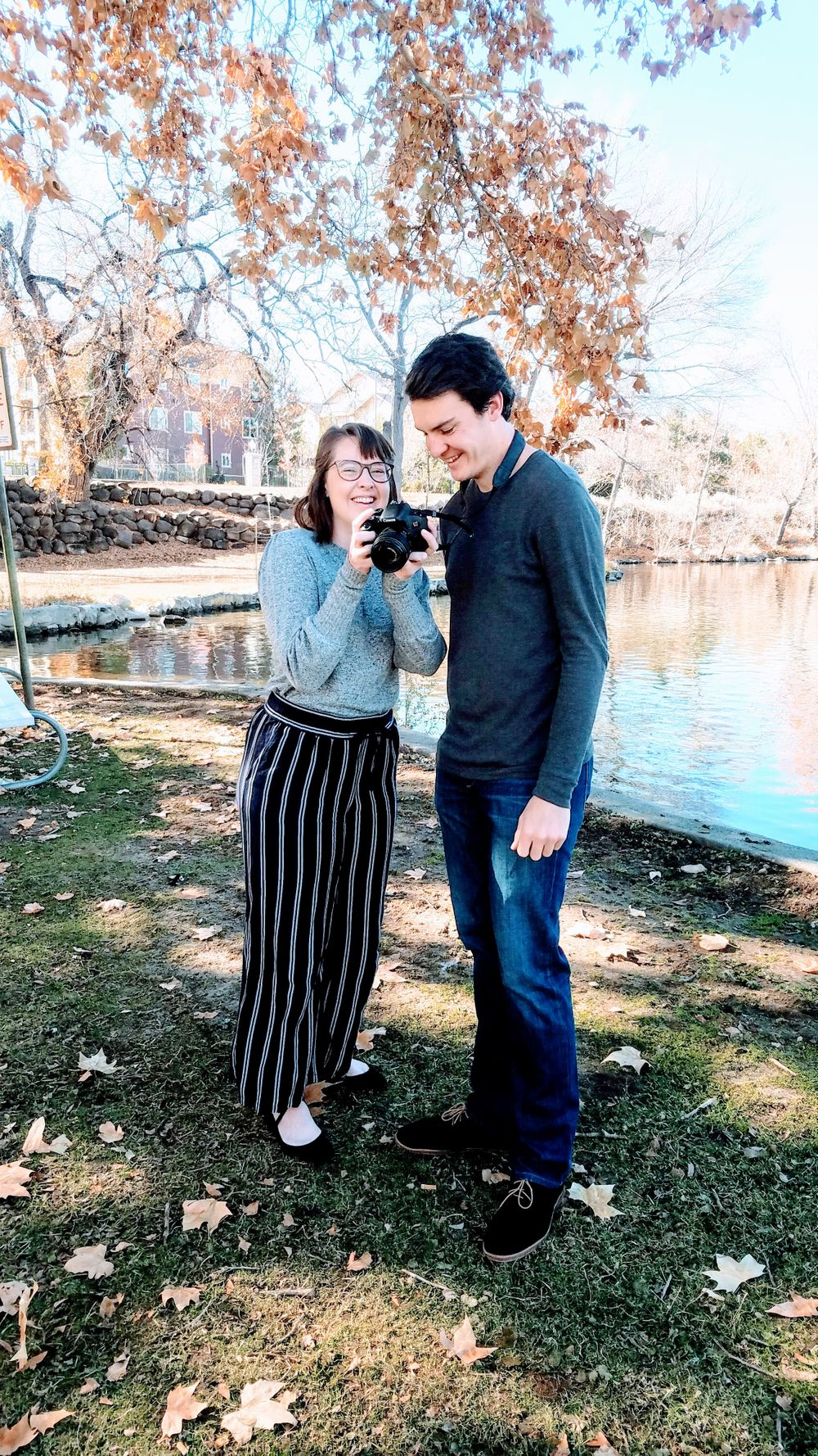 Brother and sister laughing at photos on a DSLR camera standing in Fall foliage