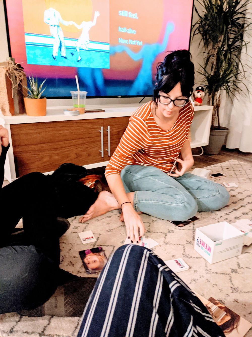 Woman turning over a playing card sitting on a rug in an apartment building