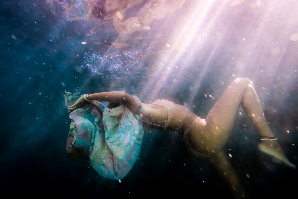A woman falling through water with sun beams on her body