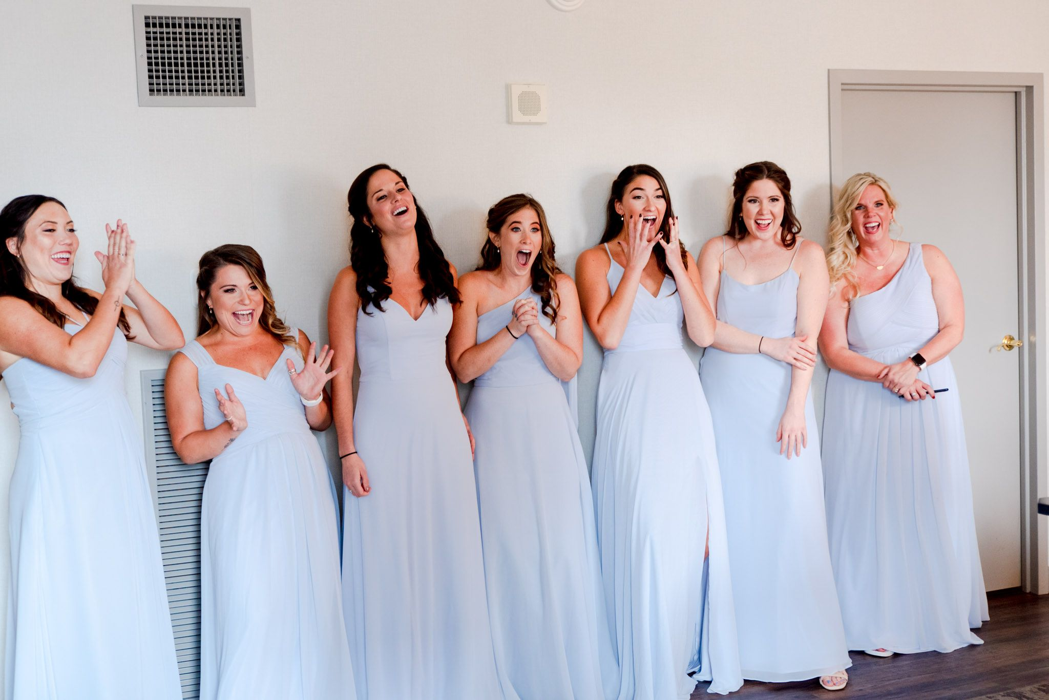 7 bridesmaids in light blue dresses smiling and clapping after seeing the bride for the first time on wedding day