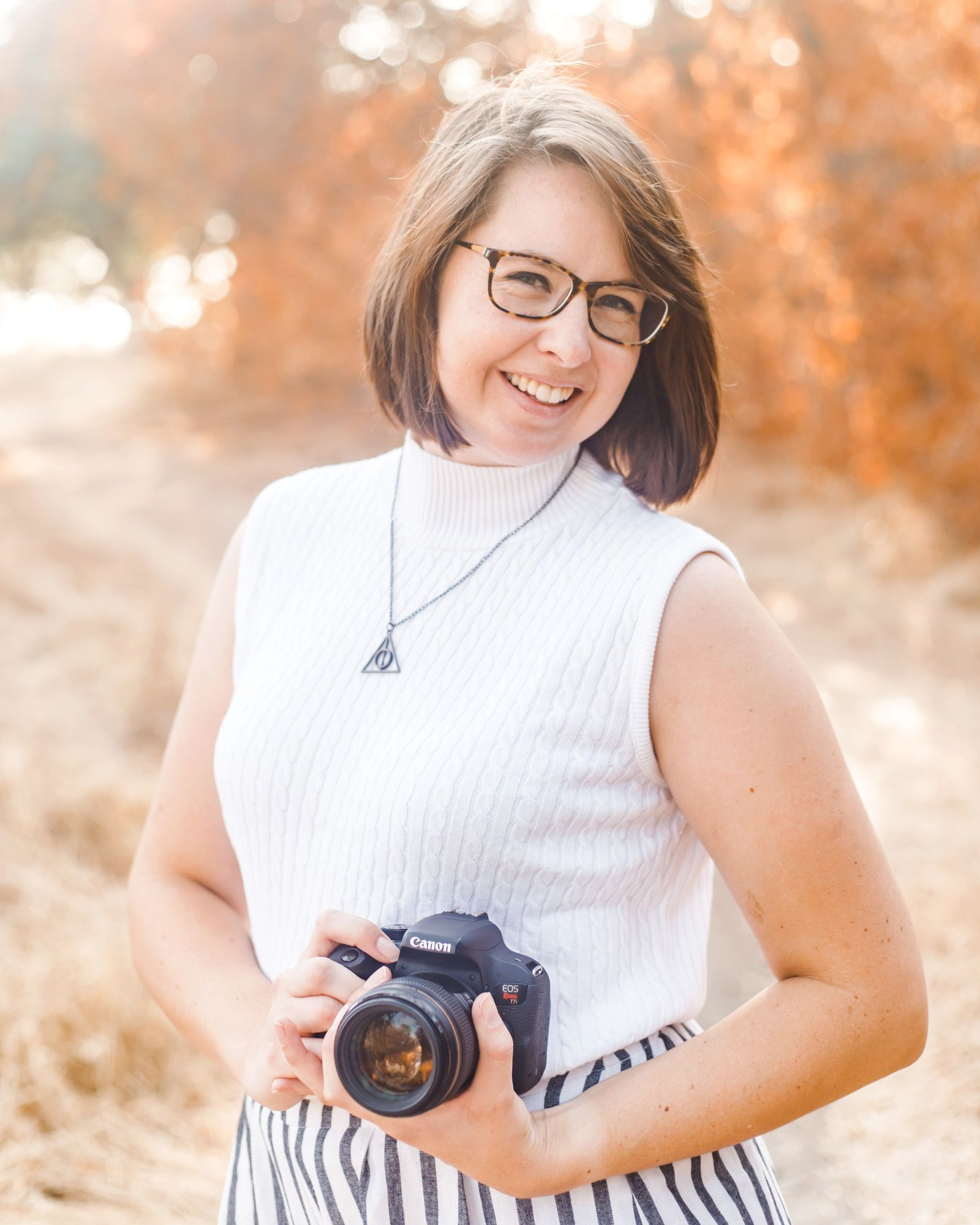 Female with short brown hair and glasses smiling at the camera wearing a Deathly Hallows necklace and holding a DSLR