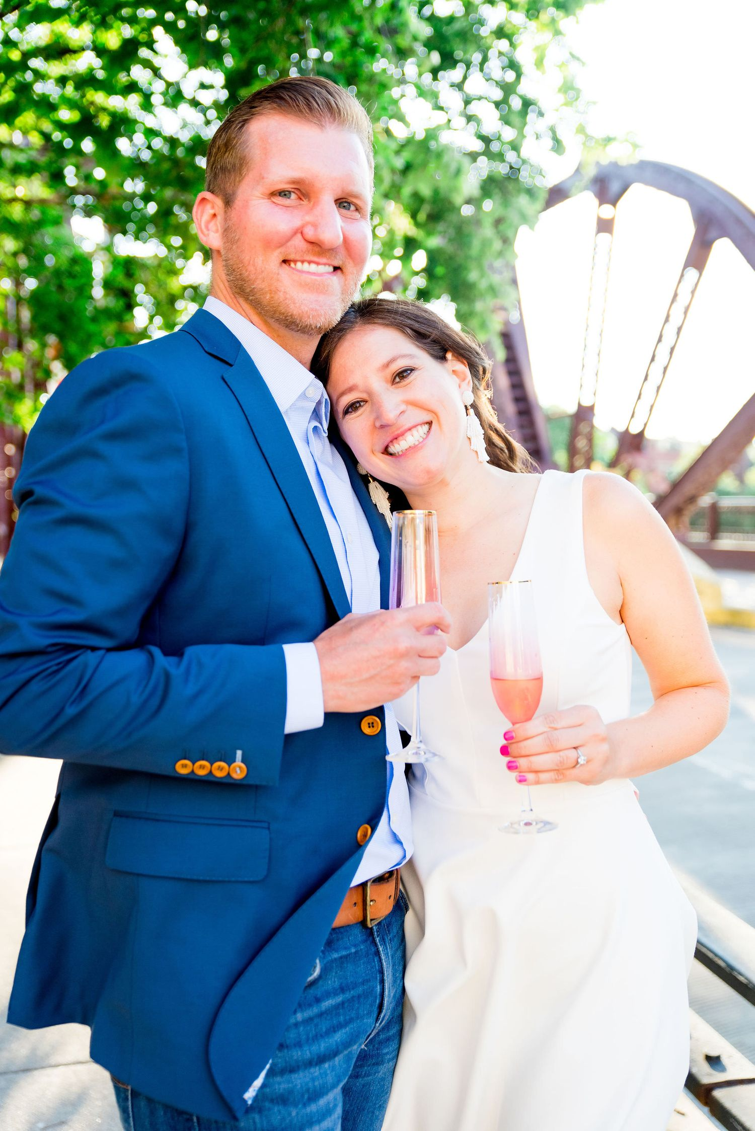 engaged man and woman holding champagne glasses and smiling at sunset at Kinzie St Bridge in River North, Chicago