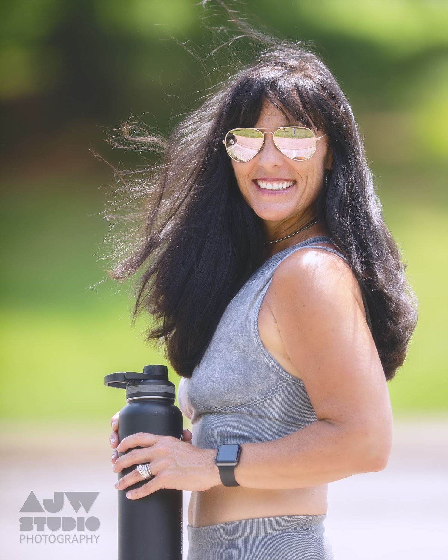 female fitness instructor with wind blown dark hair poses with water bottle