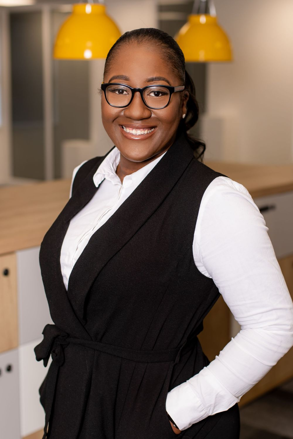 A black woman wearing glasses smiles at the camera for her headshot image - Corporate photography