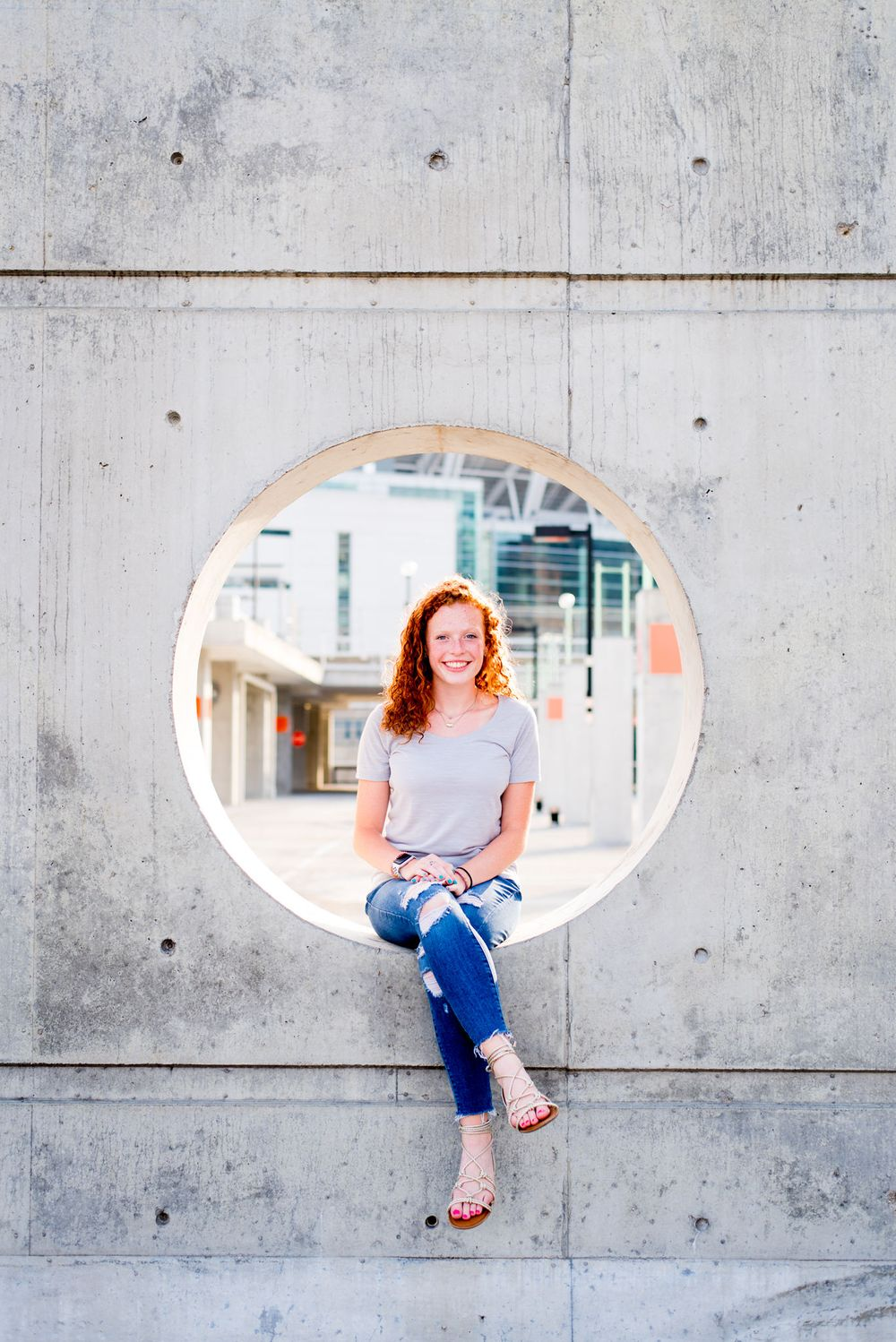 young woman with curly red hair sitting in a circle cut out from concrete wall in parking structure, smiling