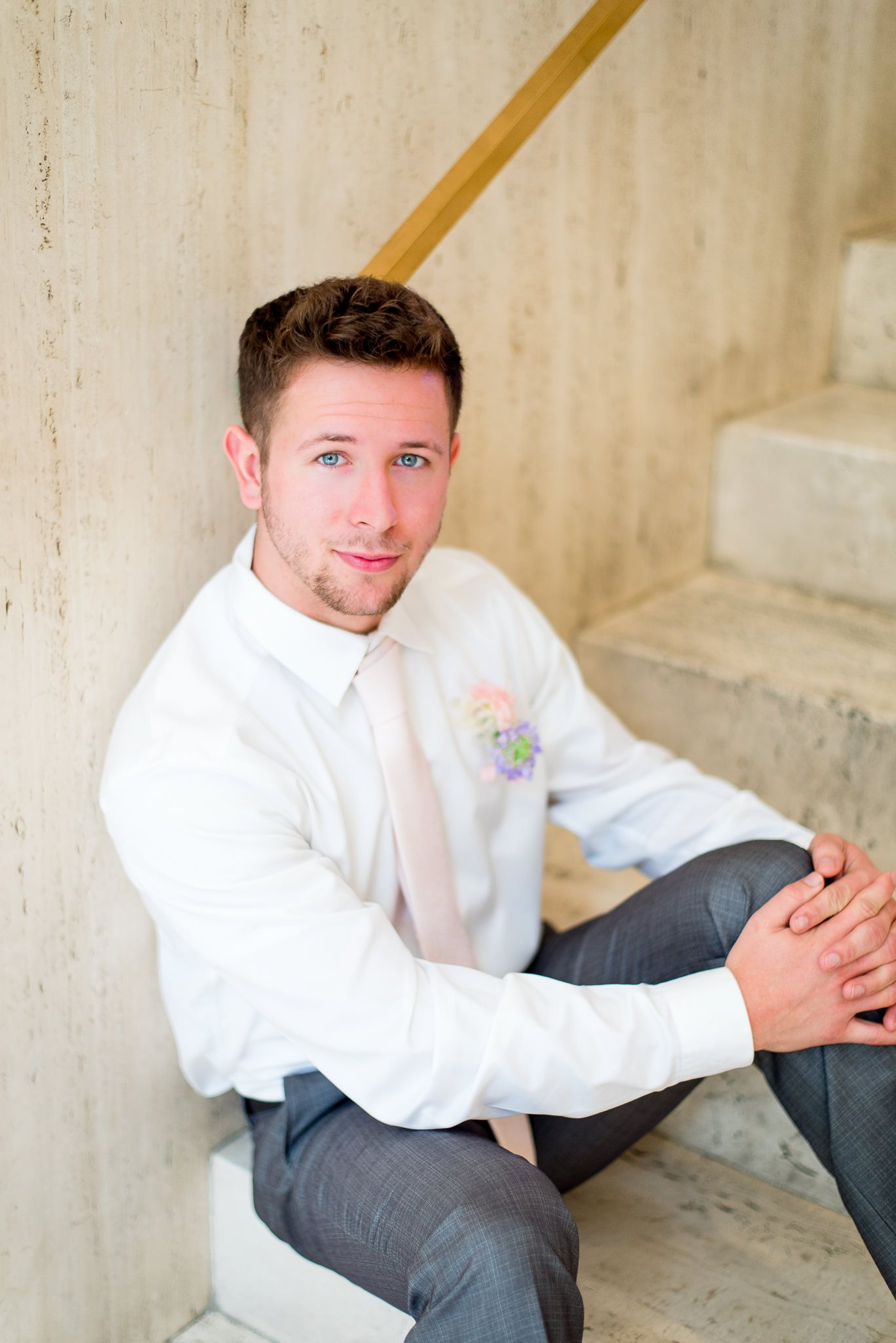 groom with blue eyes, light pink tie, and pink and purple boutonniere sitting on marble steps at The Center Cincinnati