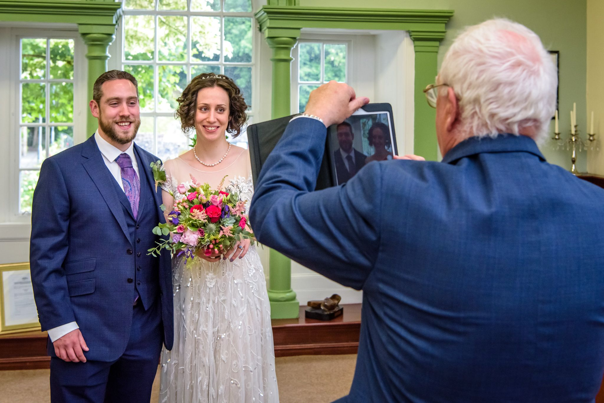 Father of bride taking iPad picture after wedding ceremony