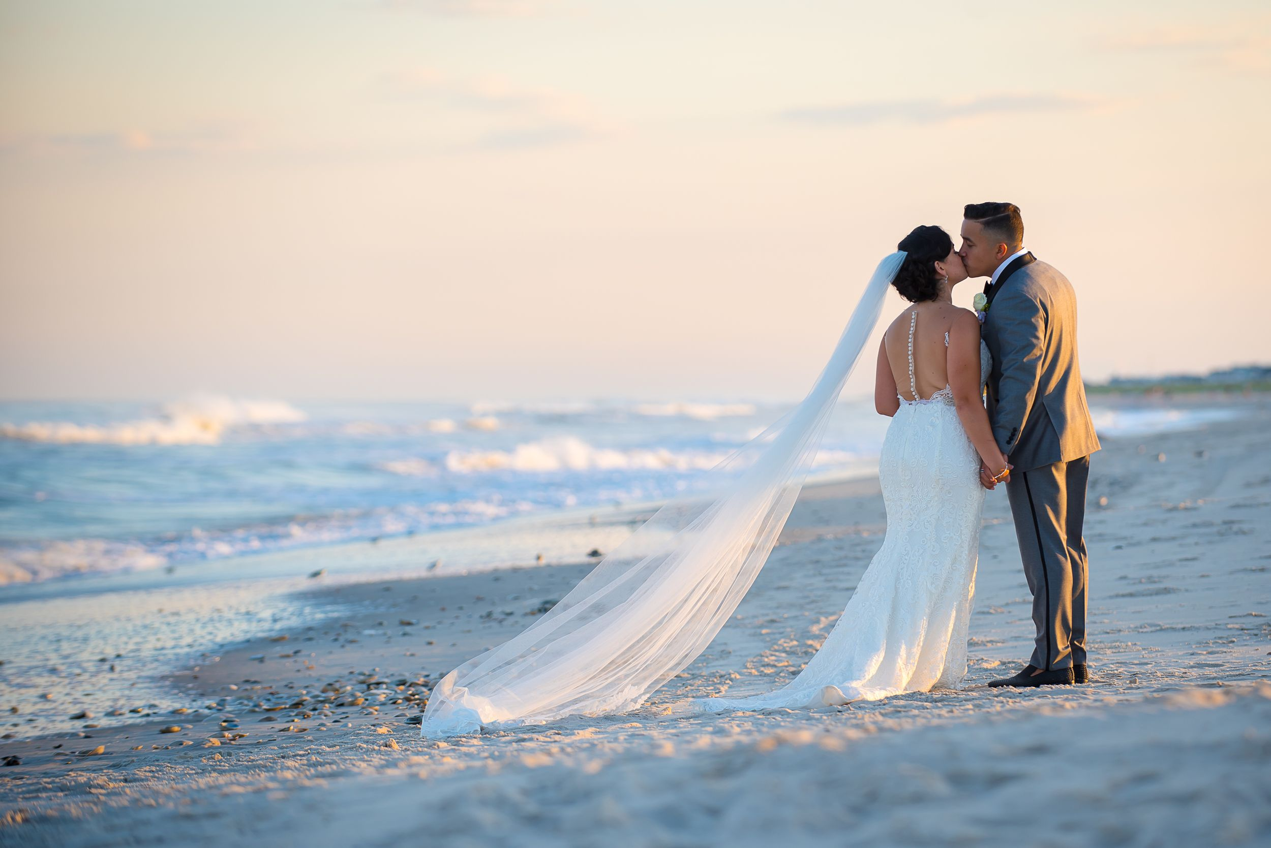dreamy sunset photo of couple kissing on the beach while waves roll onto the shore | NJ Shore Wedding Photographer LBI