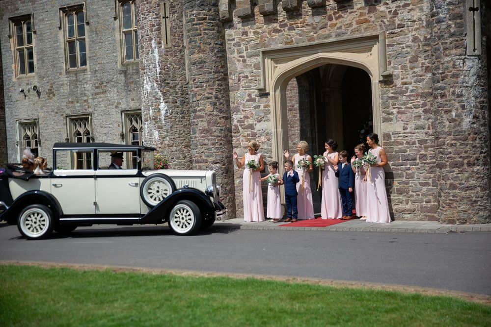 bridesmaids in front of Hensol Castle waving at bride in her beautiful vintage wedding car