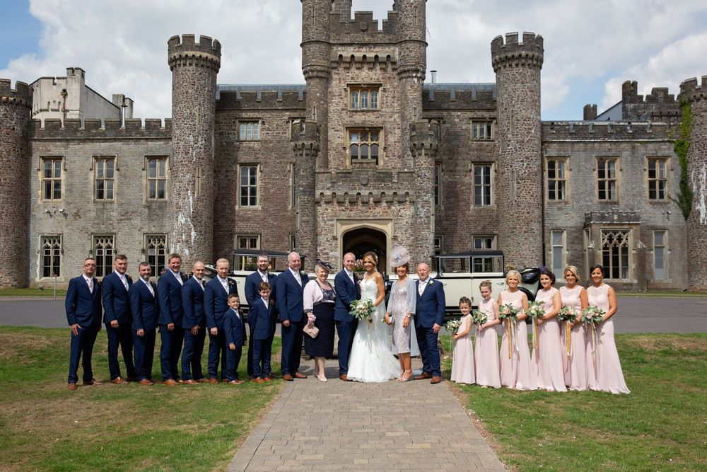 hensol castle formal wedding party picture in front of castle with vintage cars