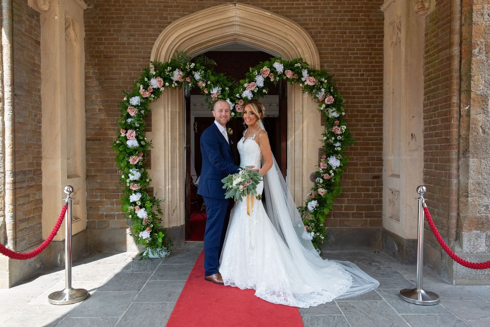 beautiful flower arch and bride and groom in front of hensol castle