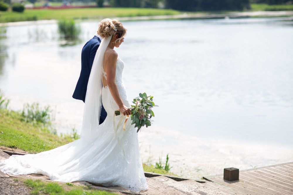 stunning bride with veil walking to the lake at hensol castle