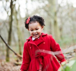 Little girl wearing red coat in woods