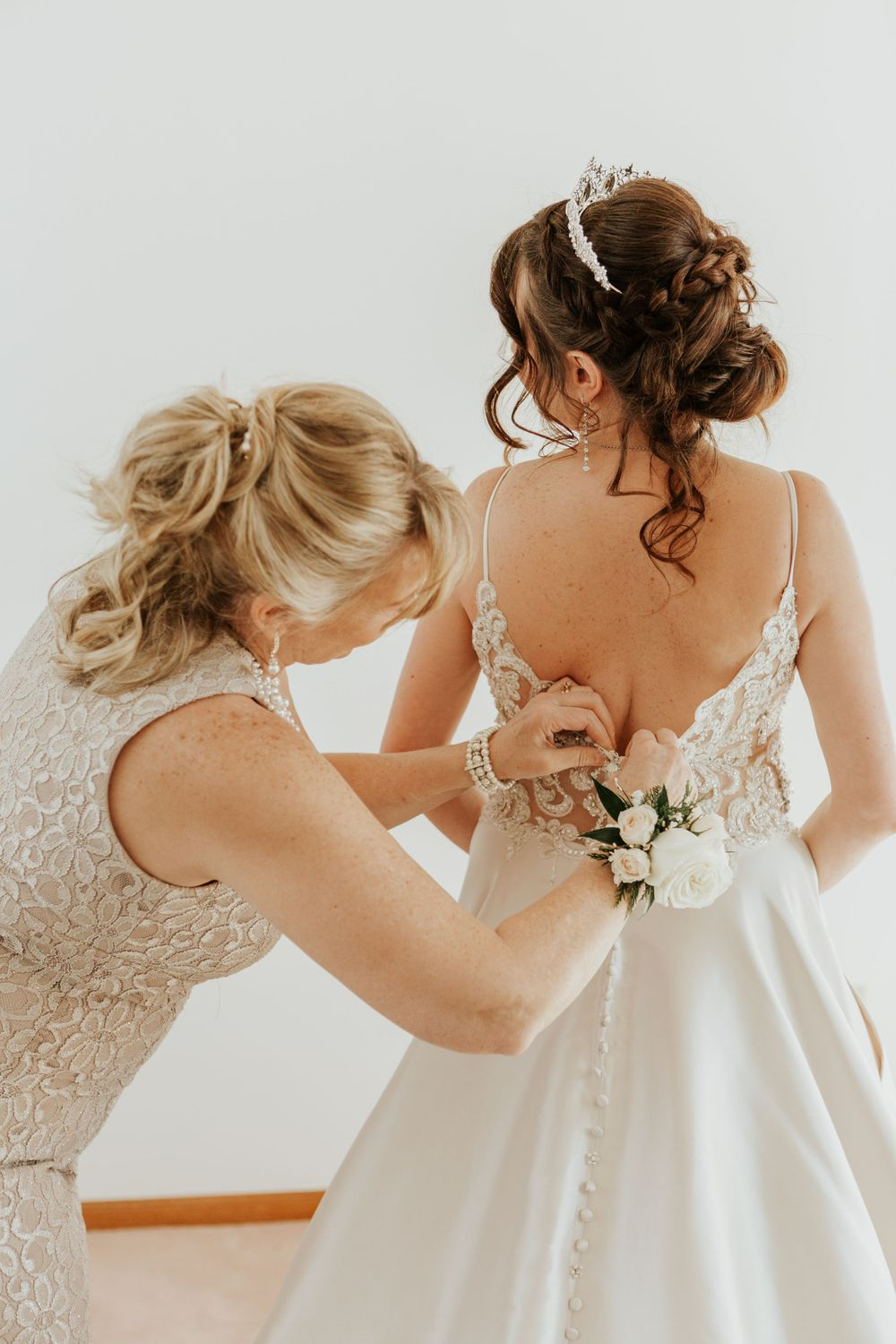 Mother of the bride fixes the brides dress during her Loveland Wedding