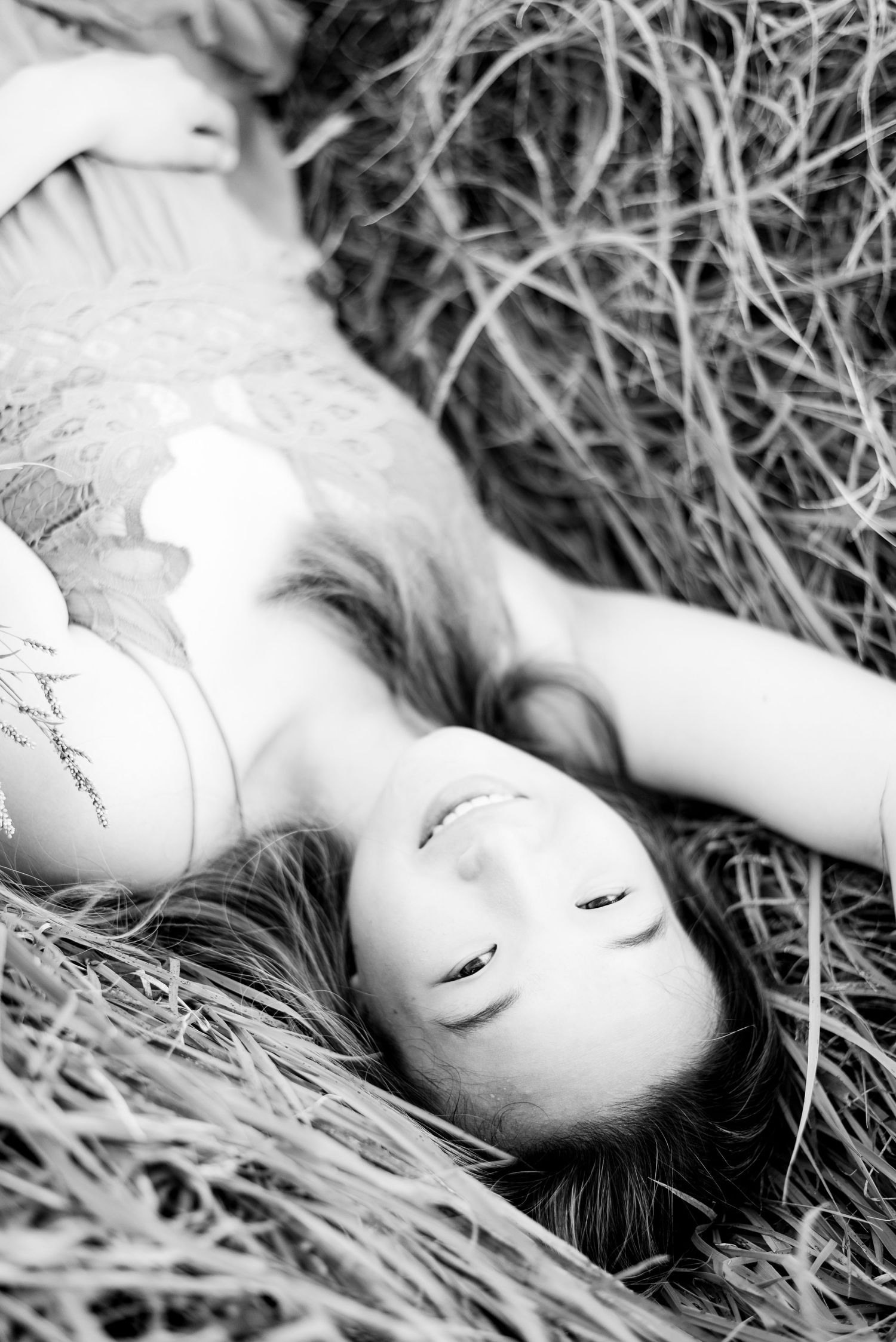 young woman smiling and laying in grass