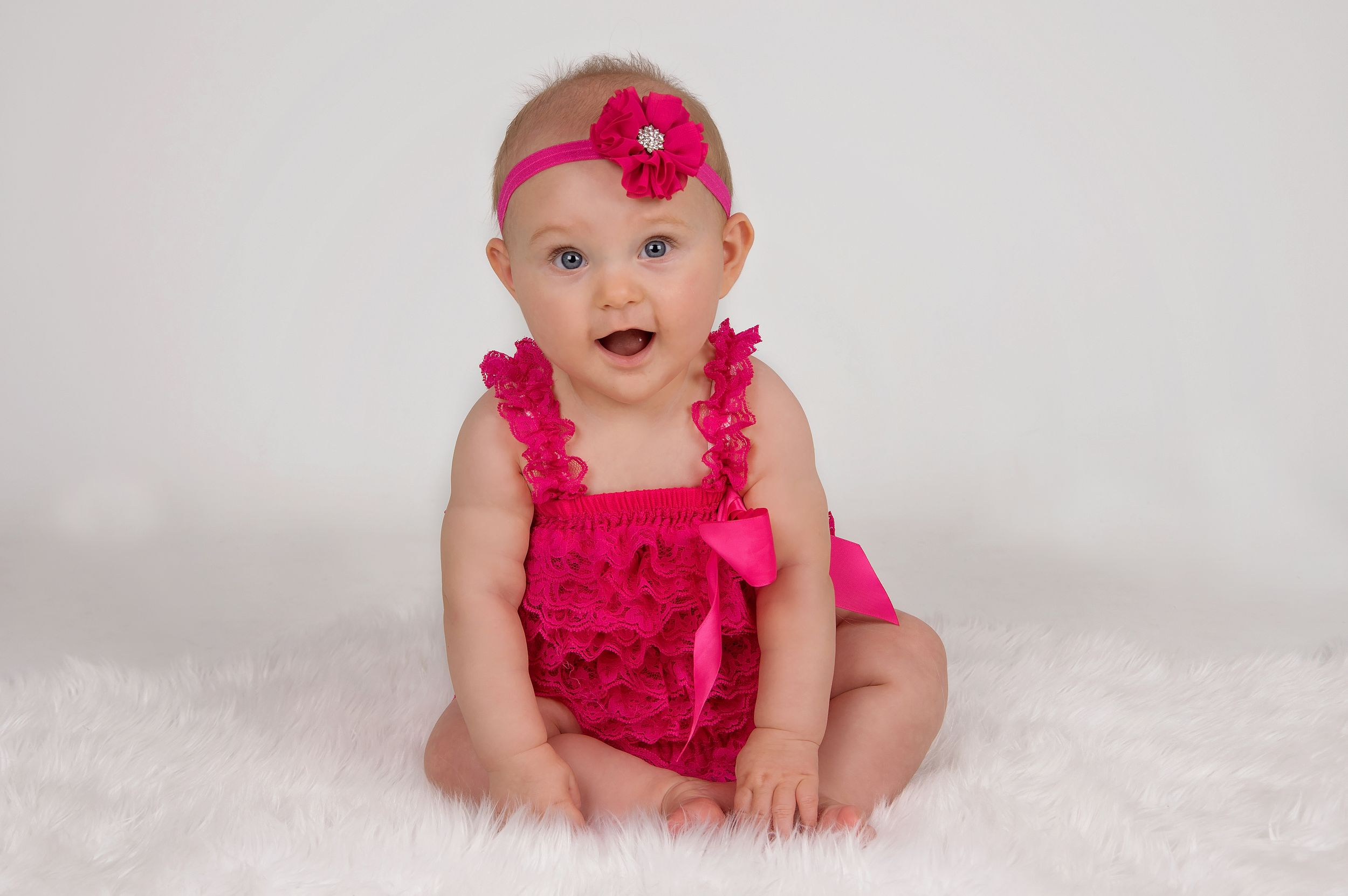 baby wearing pink sitting up posing for camera