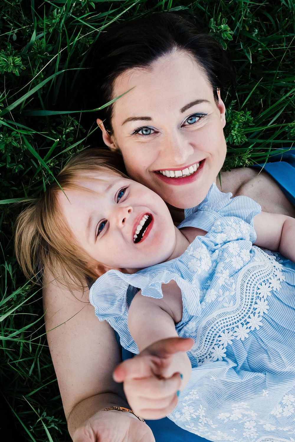 Mother and daugther with blue eyes laying on the grass in Gumpoldskirchen
