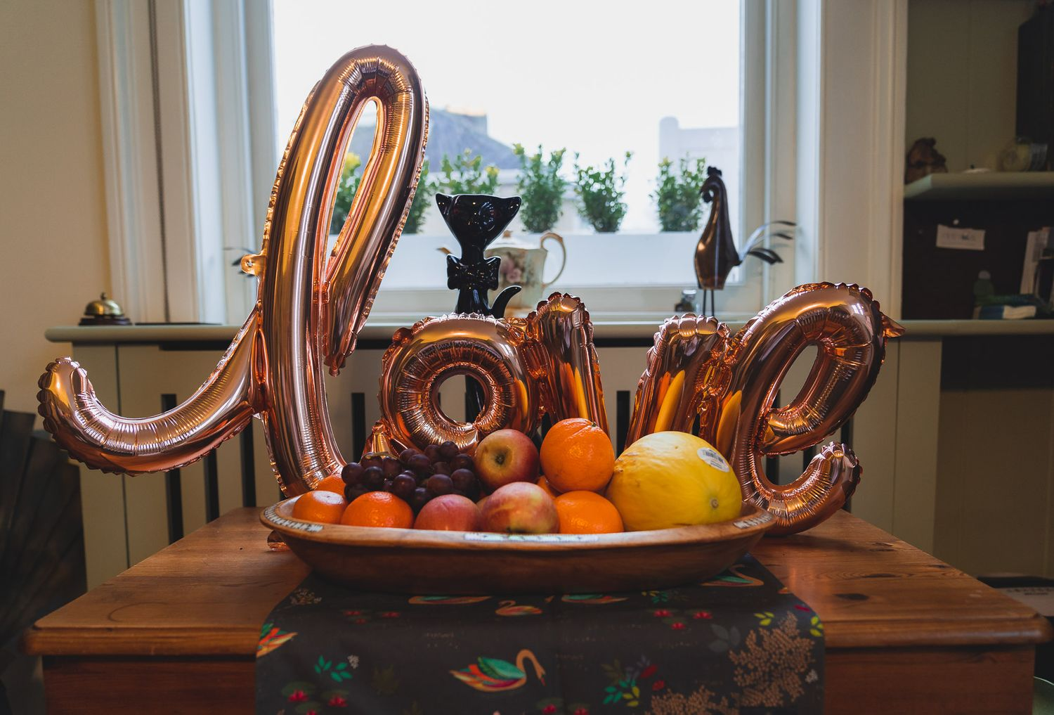A rose gold love balloon is propped up on a bowl of fruit.