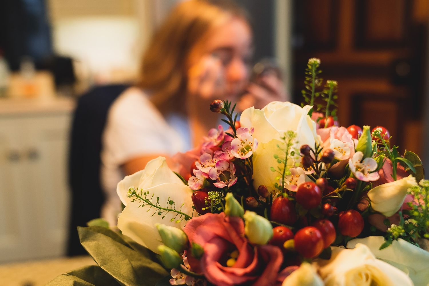 Wedding bouquet is in focus in the foreground, bridesmaid does her makeup in the background. Salisbury wedding prep.