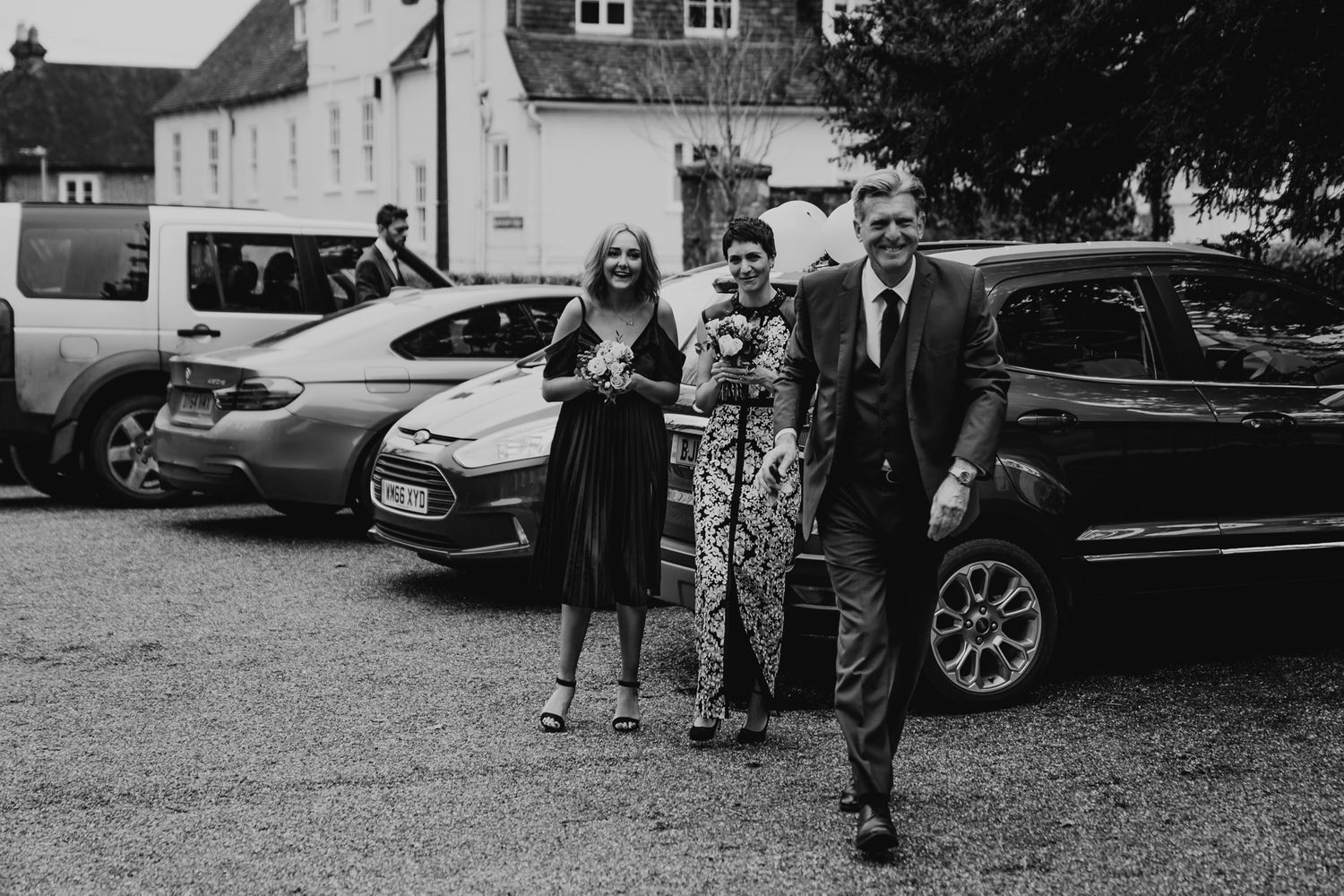 Black and white photo of the bride, her father and bridesmaid arriving at Salisbury Registry Office.
