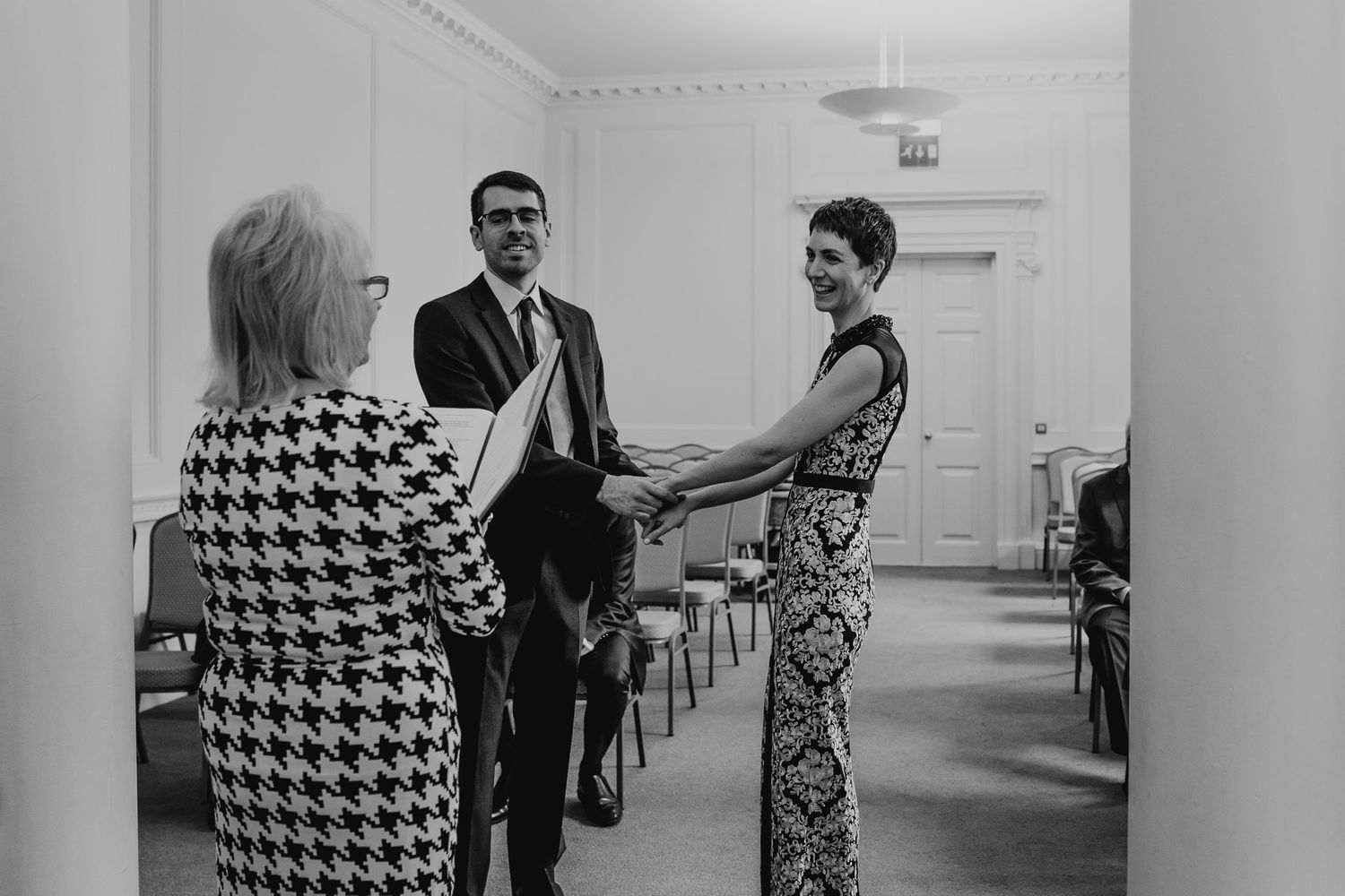 Black and white photo of bride and groom stood in front of registrar at Salisbury Registry Office.