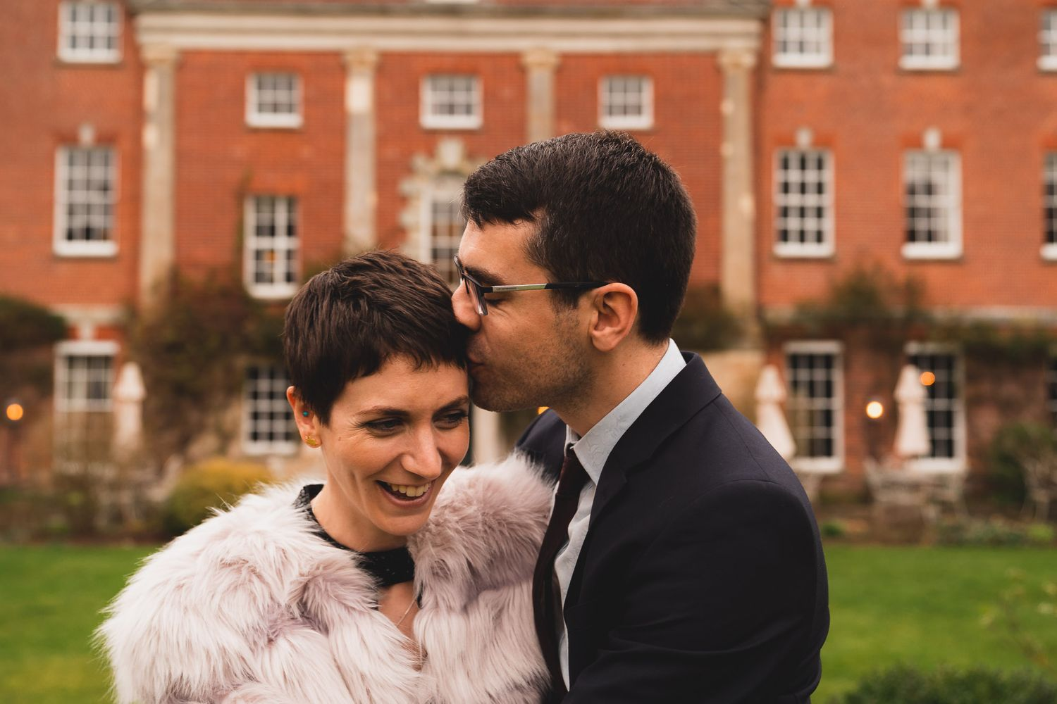 Groom kisses his new wife on the temple outside their wedding venue, 10 Castle Street in Dorset.