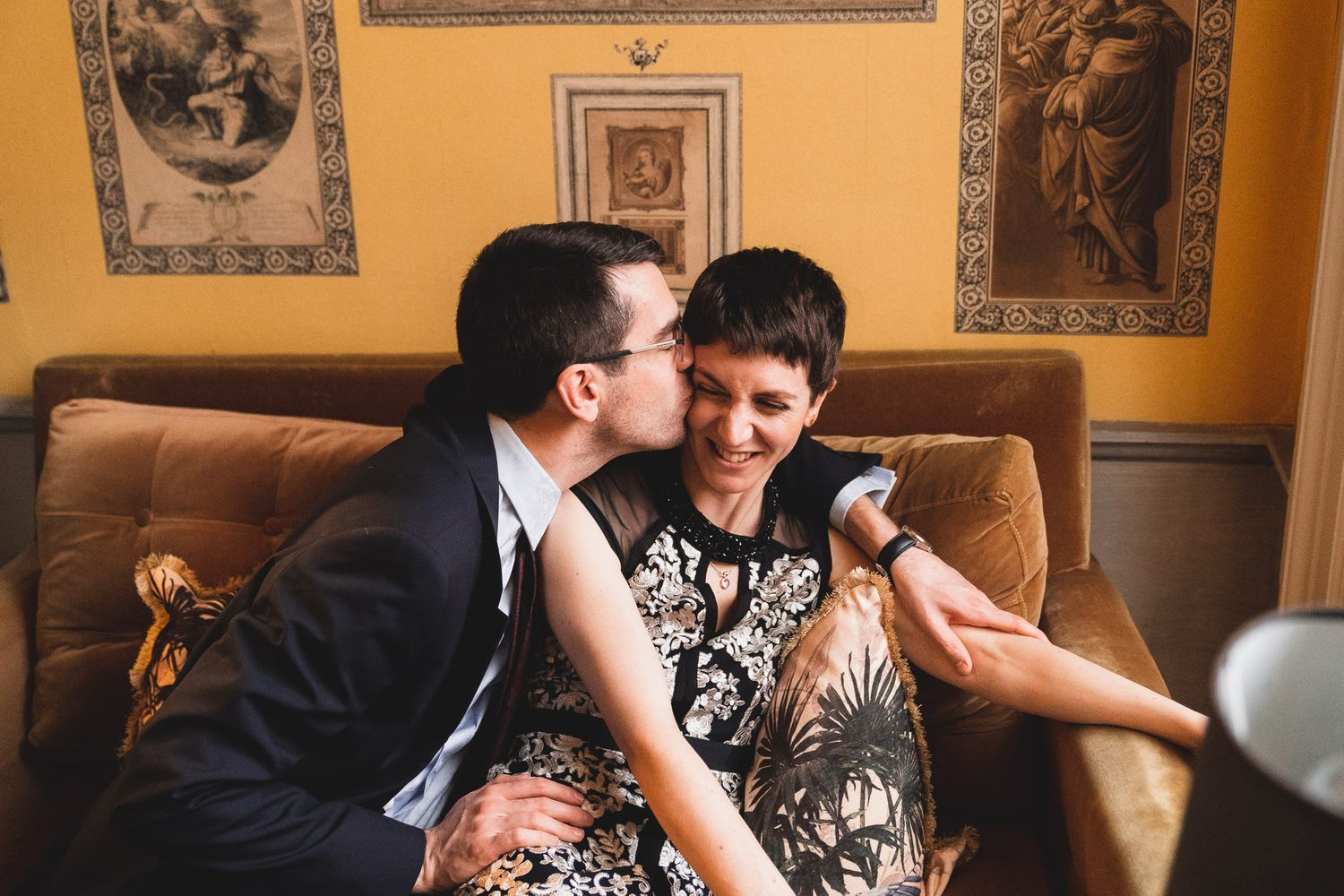 Bride and groom kiss and cuddle on a sofa at their Dorset wedding venue, 10 Castle Street.