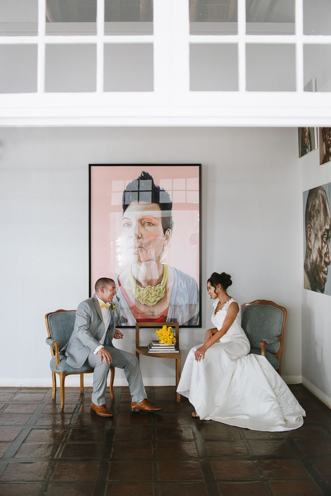 Editorial style Wedding Portrait of a interracial couple sitting in front of local artwork in San Francisco venue.