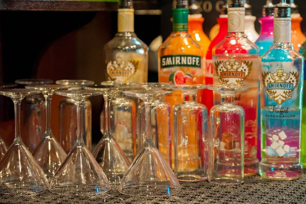 closeup of wine glasses and colorful alcohol bottles in bar at restaurant