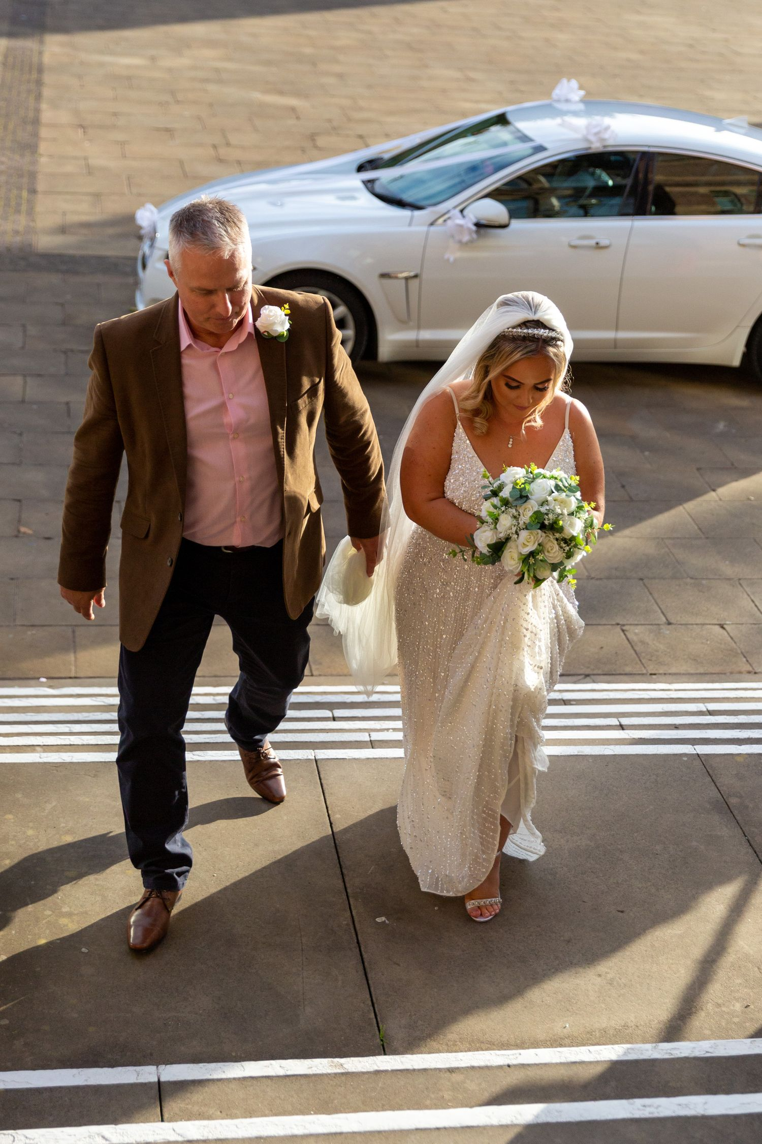 bride and her father arrive and walk up the steps to st.helens town hall