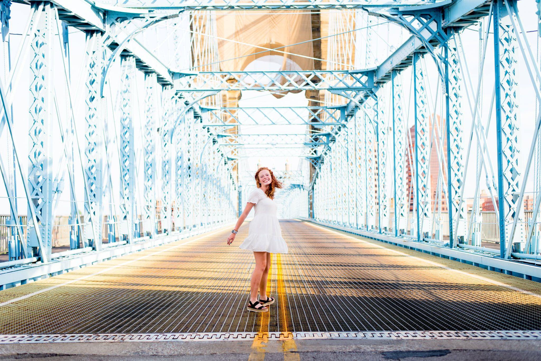 young woman in short white dress spinning around on blue Roebling Bridge for downtown Cincinnati senior pictures