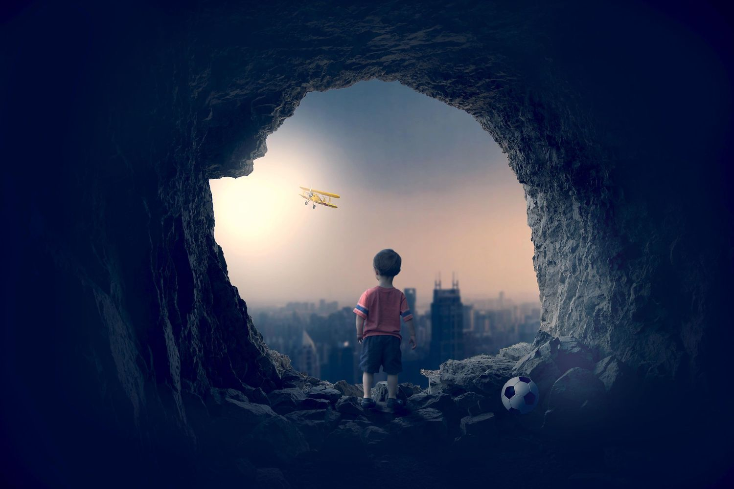 Boy in a cave looking out over the city, football